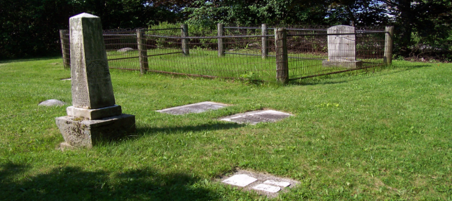 gravestones with fence around it