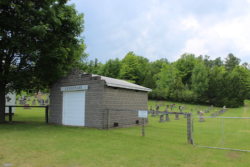small grey building and cemetery gravestones