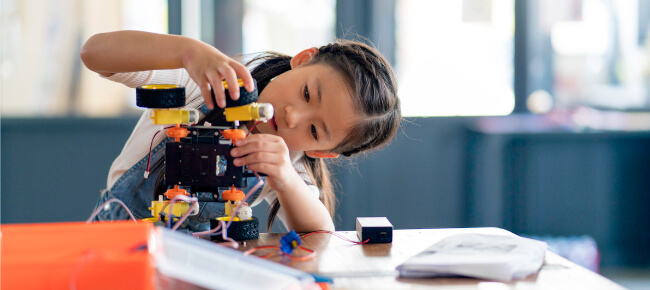a young girl setting up a microscope