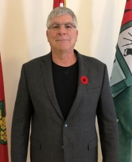 Councillor Mike Filip wearing a grey blazer with a poppy on it
