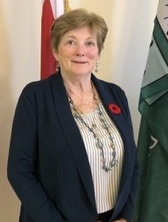 Deputy Mayor Gail Latchford standing in front of flags with a poppy on her blazer