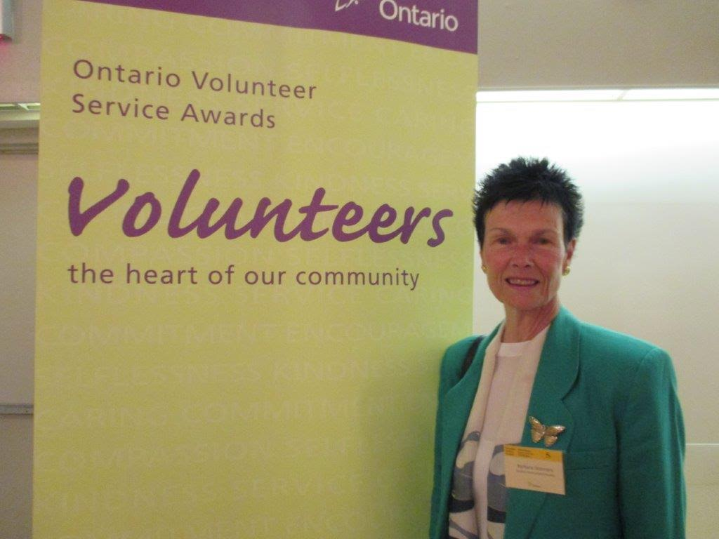 "woman standing in front of poster titled ""Ontario Volunteer Service Awards"""
